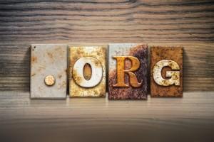 "The word ""DOT ORG"" written in rusty metal letterpress type sitting on a wooden ledge background."
