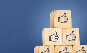 Thumb up icon on wood cube at dark blue background, leave space for adding text.